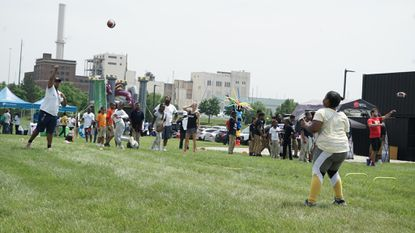 Taurus Barksdale, 26, throws a football with a student during the first Success Fest at the Field at Port Covington on June 8. This weekend, the space will host a wellness festival and a Matisyahu concert.