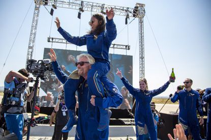 Virgin Galactic founder Richard Branson carries crew member Sirisha Bandla on his shoulders while celebrating their flight to space at Spaceport America near Truth or Consequences, N.M., Sunday, July 11, 2021. (AP Photo/Andres Leighton)