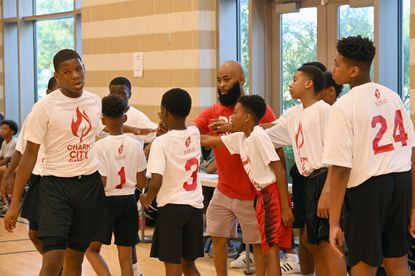 Coach Geedy, center, of Bentalou recreation center, encourages his team. Local kids are participating in Charm City game a Games that are an Olympic-style competition for kids ages 12-14 from July 15-20, as a way to bring the communities of Baltimore together.