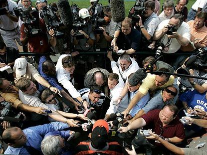 """Journalists surround Rafael Palmeiro before batting practice. """"I appreciated the fans cheering and supporting me,"""" he said later."""