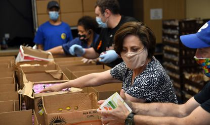 Stephanie Archer-Smith, Executive Director of Meals on Wheels of Central Maryland, packs food boxes at the warehouse with volunteers and staff. June 12, 2020