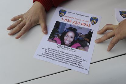 A member of the Guardian Angels holds down a flyer during the search for Phylicia Barnes in 2011.