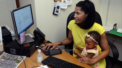 Shannon Sneed, a member of the Baltimore City Council, holds her daughter Rae as she works at her desk in City Hall.