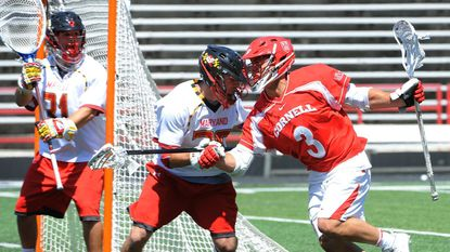 Terps midfielder Jesse Bernhardt tries to keep Cornell's Rob Pannell away from the crease as goaltender Niko Amato looks on.