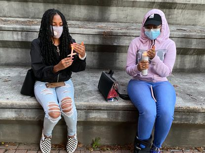 Danaysha Samuel, left, and Demara Ellis sit and light candles during a vigil for Breonna Taylor at Morgan State University on Wednesday night. Sept. 30, 2020