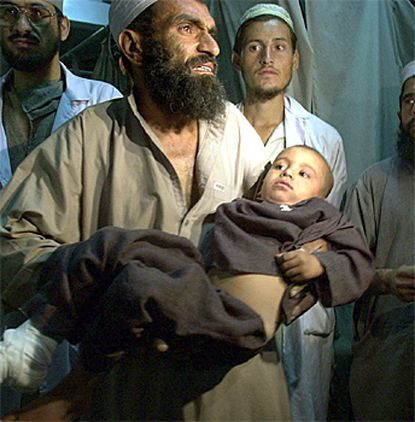 Injured: Lala Bidal takes his son Hazrat, 4, to the X-ray room at a hospital in Jalalabad, Afghanistan. Both were wounded in what the Taliban said was a U.S. air attack Thursday on Majpoorbal, near Jalalabad.