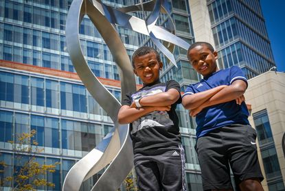 Brothers Christian, 8, (left) and Gerald Mugera, 11, volunteered for a clinical trial of the Moderna COVID-19 vaccine for children under 12 at the University of Maryland School of Medicine's Center for Vaccine Development and Global Health.