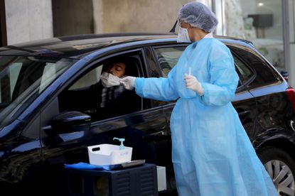 Biologist doctor Caroline Gutsmuth swabs a woman with covid-19 symptoms as she stays in her car, outside a medical biology laboratory who opened a coronavirus drive-thru testing site, in Neuilly-sur-Seine, near Paris, Monday, March 23, 2020.