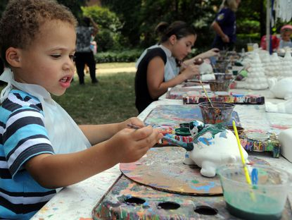 Young Matthew Henderson of Fallston works on his painted turtle masterpiece at teh kids paint an animal stand during Sunday's Bel Air Festival for the Arts in Shamrock Park.