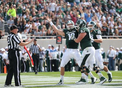 Michigan State quarterback Connor Cook celebrates after scoring on a 4-yard run during the first quarter against Eastern Michigan at Spartan Stadium on Sept. 20.