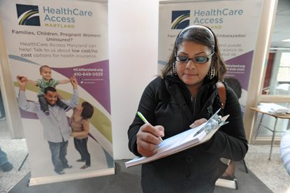 Glen Burnie, Md.--11/15/14-- Esmeralda Beanda, 41, of Catonsville, who was fourth in line, fills out paperworks after signing up for health insurance at Healthcare Access Maryland's open enrollment fair at Corkran Middle School in Glen Burnie. Saturday is the first day of open enrollment in Maryland and the nation on healthcare exchanges created under the Affordable Care Act for the uninsured and those who do not get insurance through their employers. (Kenneth K. Lam/Baltimore Sun) DSC_7344 hs-exchange-p2-fair lam