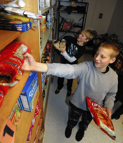 North Carroll Middle School students John Geci, 13, of Lineboro and Matthew Bartlett, 13, in back, of Westminster, restock the shelves of the school's food pantry. This is the second year for the pantry, which offers food assistance to families and individuals in the region.