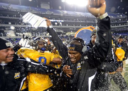 Wise coach DaLawn Parrish celebrates after getting doused with water after the Wise Pumas won the Maryland High School Class 4A Football State Championship game at M&T Bank Stadium in Baltimore on Friday, November 30, 2012. Parrish played high school football at Howard, the team he will guide Wise against in this year's Class 4A title game on Dec. 4.