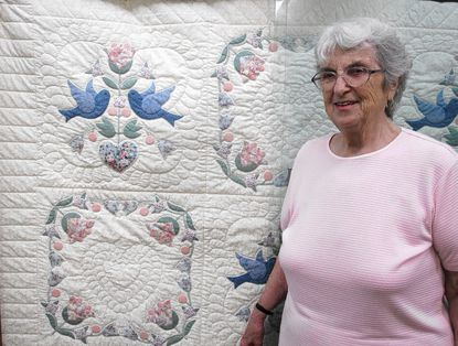 """Beverly Green is shown with the """"Love Dove"""" quilt that is first prize in the raffle. Her late sister, Hazel Mullinix, and Lucille Weed stitched this quilt."""