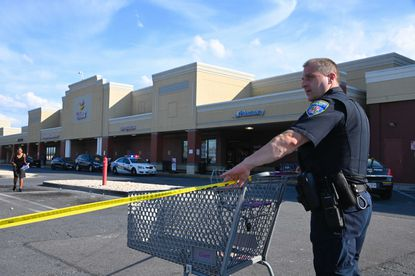 Baltimore Police officers investigate a crime scene at the Giant in Reisterstown Plaza where a grocery store armed security guard shot two people inside, killing one of them, after an altercation late Tuesday afternoon. (Ulysses Muñoz/Baltimore Sun).