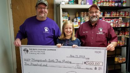 Jim Roark, left, and Bob Ellers, president of the Bucs, present a check for $500 to Makenzie Greenwood, founder of Hampstead's Little Free Pantry.