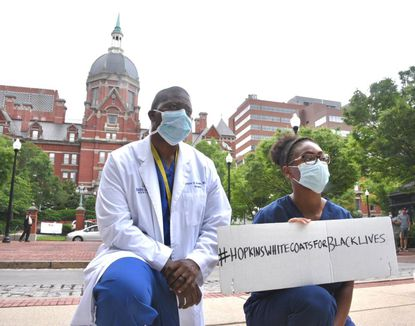 """Hundreds of doctors, nurses, medical and supporting staff at Johns Hopkins Hospital showed up Friday for the #WhiteCoatsForBlackLives movement. They took a knee for nearly 9 minutes and read the names of police brutality victims. Recently, Hopkins decided to """"pause"""" for at least two years a controversial plan to implement an armed police force at its facilities."""