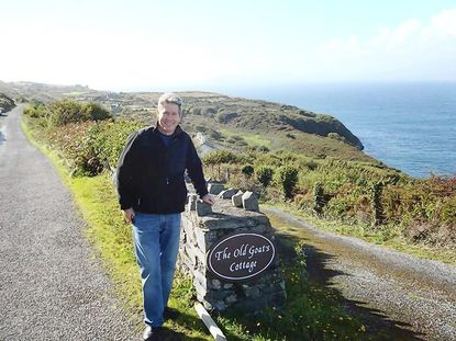 During a recent trip to Ireland, John Shields stands near the sign for The Old Goat's Cottage, with a view of Bantry Bay in the background.