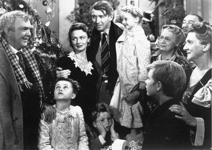 """<p>Frank Capra directed """"It's a Wonderful Life,"""" starring Jimmy Stewart with his arm around Karolyn Grimes, who played his daughter Zuzu. His other arm is around his co-star Donna Reed. Actor Thomas Mitchell, as Uncle Billy, stands at left.&nbsp;</p>"""