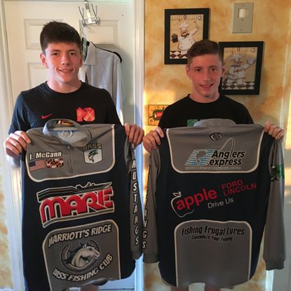 Ian McGann, 17, left and Riley McGann, 17, pose with the jerseys that they will wear at the Bassmaster High School Championship at Kentucky Lake in Paris, Tenn., from Aug. 4-6.