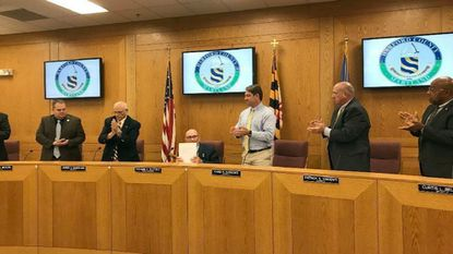 Harford County Council President Richard Slutzky, center, gets a standing ovation from his council colleagues Tuesday after giving a farewell address. Slutzky is stepping down after 16 years on the council when his term ends in December.