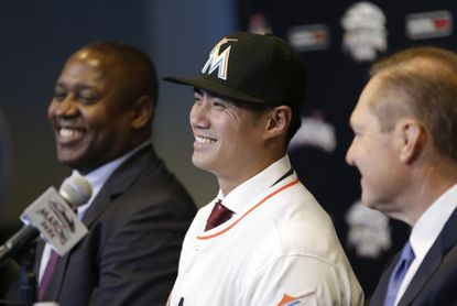 Pitcher Wei-Yin Chen, center, smiles as he sits with Miami Marlins president of operations Michael Hill, left, and agent Scott Boras, right, during a news conference, Tuesday, Jan. 19, 2016, in Miami. The left-handed pitcher finalized an $80 million, five-year contract.