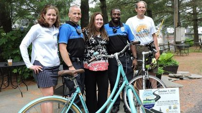 Flanking iCan! Shine Bike Camp organizer Shannon Majoros, in the center, are volunteers (left to right) Rachel Varn of Pedal Power Kids, bicycle patrolmen Dominic Scali and Stanley Newborn and Bike AAA President Jon Korin. They met to discuss the camp hosted by RISEforAutism.