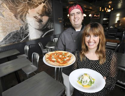 Siblings Josh and Stephanie Hershkovitz are the owners of Hersh's Pizza and Drinks in Riverside at 1843 Light St. Josh, who is also the chef, holds a Margherita pizza for $10. Stephanie holds a plate of fennel and orange salad with shaved bottarga for $7.50.