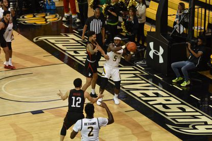 Towson guard Jakigh Dottin looks for an opening to pass to teammate Allen Bertrand during the Tigers' game against Northeastern on Saturday. Courtesy of Towson University