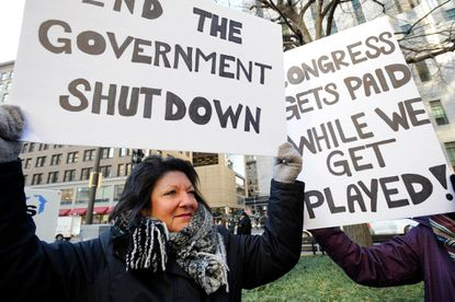 EPA employee Rosanne Sawaya-Obrien holds her sing during a rally and protest by government workers and concerned citizens against the government shutdown on Friday.