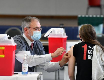 U.S. Congressman, Dr. Andy Harris, right, administers a COVID vaccine shot to a person during the vaccination clinic at the Center for Educational Opportunity building in Aberdeen Tuesday March 16, 2021.