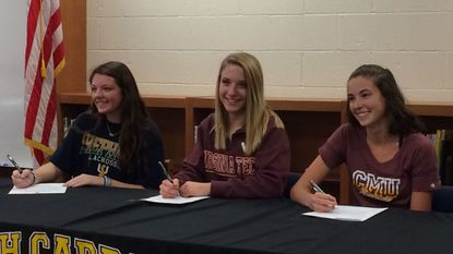 From left, Haleigh Piccolo, Allie Zolkiewicz, and Anna Lausch pose for photos during a college commitment signing day ceremony at South Carroll High School on Nov. 13, 2017.
