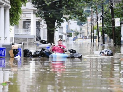 Bruce Koch, a 25 year resident of Port Deposit, manuevers through bags of trash as he uses his kayak to get around on Main Street in Port Deposit as the Susquehanna River continued to rise Thursday afternoon.