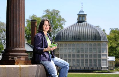 Roland Park resident Janet Felsten, founder of Baltimore Green Map and creator of a new 'Passport' for Druid Hill Park, sits at an entrance colonnade overlooking the Rawlings Conservatory and Botanic Gardens on May 5.