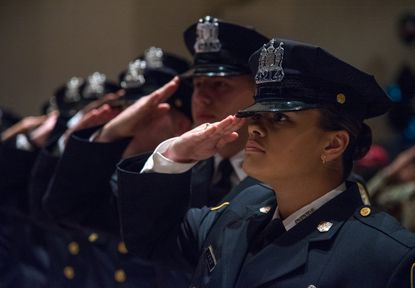 Police trainee Diamond Sykes salutes as she stands with her fellow class members as they prepare to graduate from the Baltimore Police Academy last year.