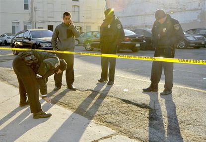 Officers examine the crime scene in a parking lot at the southeast corner of W. Franklin and N. Paca Streets, north of Select Lounge where gunfire erupted Sunday morning.
