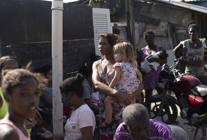 Women and children wait for donated food distributed by the the Covid Without Hunger organization in Rio de Janeiro, Brazil, last month. Inflation is climbing at its fastest pace since 2016, at 6.8%, but over the past 12 months the cost of staple foods rose between 18% and 57%. (AP Photo/Silvia Izquierdo)