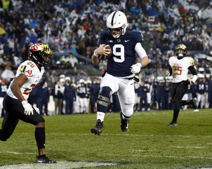 Penn State quarterback Trace McSorley (9) runs in for a touchdown in front of Maryland's Antwaine Richardson (20) during the first half of an NCAA college football game in State College, Pa., Saturday, Nov. 24, 2018.