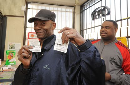 At the Shop 'N Food on Washington Boulevard, Grantland Jackson, 63, left, bought two Mega Millions tickets, then gave $5 to Rajah Dorsey, 38, right, a stranger, to buy five Mega Millions tickets.