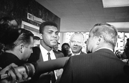 Muhammad Ali with his chief attorney Hayden Covington, right, on June 19, 1967 in Houston, Tex., as they wait for the elevator to take them up to the federal court and Clay's trial for refusing to be inducted into the armed services. (AP Photo/Ed Kolenovsky)