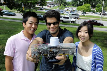 Hopkins students (from left) Jeffrey Kamei, Anshul Mehra and Yejin Kim show the Child Motion Sensing System.