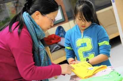 Amanda Wang, 9, and her mom, Zhiling Li, prepare their hand-drawn animal T-shirts for sale Thursday at Pointers Run Elementary School's Family Fit Night.