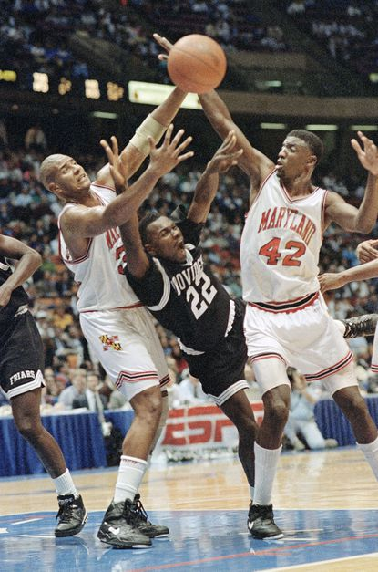 Maryland's Walt Williams (No. 42) reaches for the ball during a gameat the Meadowlands Arena, Wednesday, Dec. 5, 1991, East Rutherford, N.J. Maryland won 76-66.