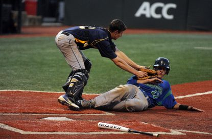 Catonsville senior catcher Jeremy Davis tags out Michael Albers, of Churchill, who was trying to score on a fly ball to right field, but was thrown out by Scott Beautz in the Comets' 4-3 2013 state semifinal win.