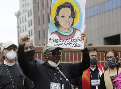 In this June 9, 2020, file photo, Kevin Peterson, center, founder and executive director of the New Democracy Coalition, displays a placard showing Breonna Taylor as he addresses a rally in Boston. Louisville's mayor says one of three police officers involved in the fatal shooting of Taylor will be fired, Friday, June 19, 2020. Taylor was gunned down by officers who burst into her Louisville home using a no-knock warrant. She was shot eight times by officers conducting a narcotics investigation. No drugs were found at her home.