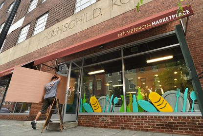 Mark Melonas of Luke Works carries plywood into the Mt. Vernon Marketplace, where he is building the counter for The Local Oyster stall. Two businesses have opened in the new Mt. Vernon Marketplace, and construction is underway for other food stalls.