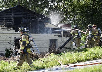 Firefighters extinguish hot spots at the scene of a garage fire in the 3500 block of Littlestown Pike in Union Mills Thursday, July 9, 2020. According to Pleasant Valley fire company Chief Forrest Shaw, no one was injured in the blaze which was reported at 5:13 p.m. Firefighters from Pleasant Valley, Reese, Taneytown, Westminster, New Windsor and Littlestown in Pennsylvania were able to control the fire in about 15 minutes.