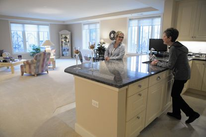 Senior move manager Jennifer Prell, left, talks with Sandy Zedella at her condo at The Garlands, a retirement community in Barrington, on Jan. 25, 2017. Prell helped Zedella move from a 4,000-square-foot three-level townhouse to a 2,500-square-foot residence.