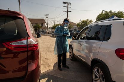 A health care worker checks in a patient at a COVID-19 drive-thru testing site, in Ladera Heights, Calif., on Tuesday, Nov. 24, 2020. With cases and deaths rising fast, scientists say they worry about the virus's course in the United States as Thanksgiving celebrations and cold weather arrive.