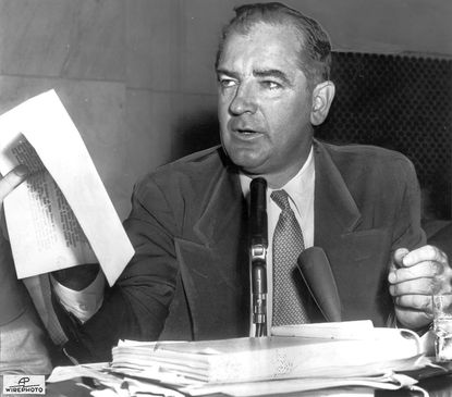 WASHINGTON, D.C.--May 5, 1954--Sen. Joseph McCarthy holds a copy of a letter under discussion at today's McCarthy-Army hearing session. A committee attorney quoted FBI Director J. Edgar Hoover as saying the letter produced by McCarthy yesterday was not a true copy of one written by Hoover to the Army. McCarthy this morning stressed that the letter he produced was verbatim with the FBI report, except for deletion of security information. (AP WIREPHOTO.)